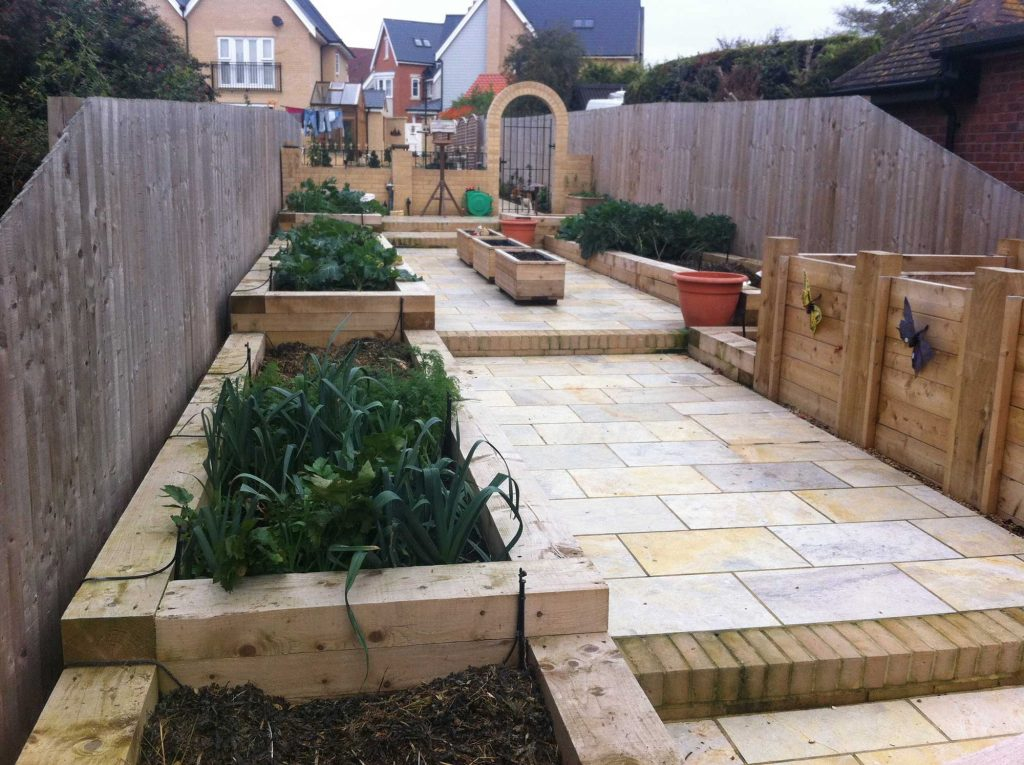 vegetable garden built on a slope with raised beds, paving and steps
