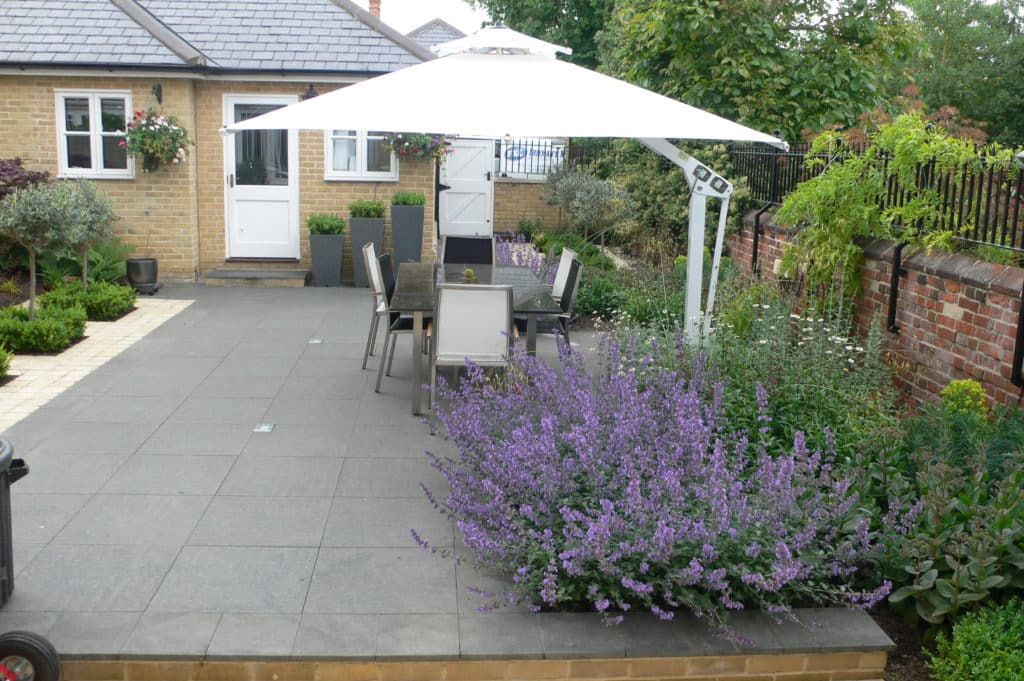 granite patio with seating area and colour coordinated planting