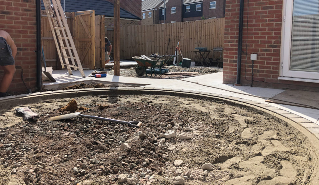 a garden under construction with a landscaper creating a patio area in the part of the garden with most privacy