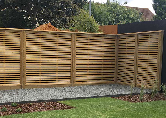 timber fence with lateral slats to form a screen