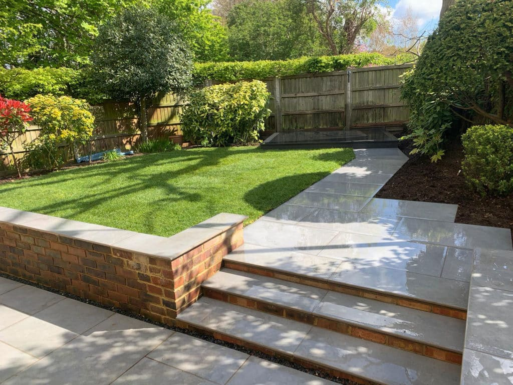pretty garden with retaining wall in the foreground leading to lawns and planting