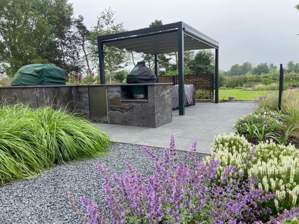outdoor kitchen with pergola, seating area and planting