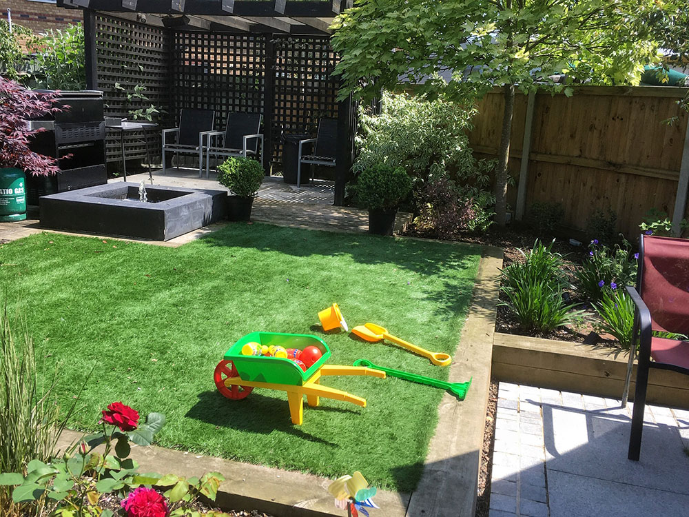 family garden with toys on the lawn, sheltered seating and square water feature