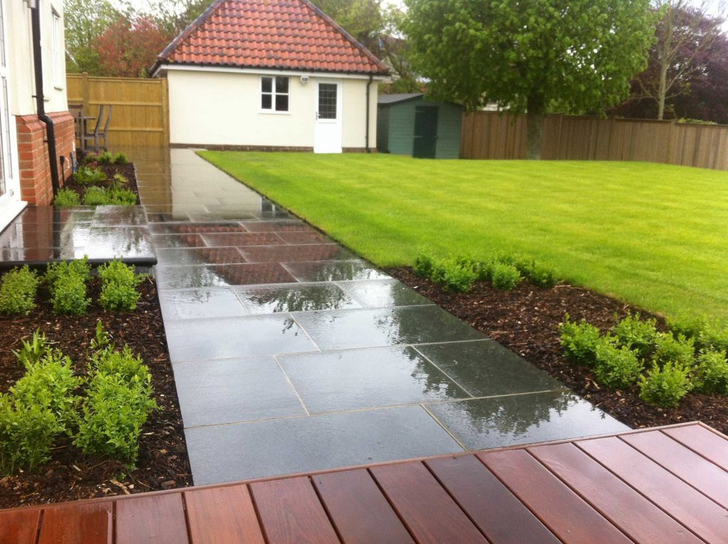 decking combined with limestone paving and lawn for a contemporary garden design