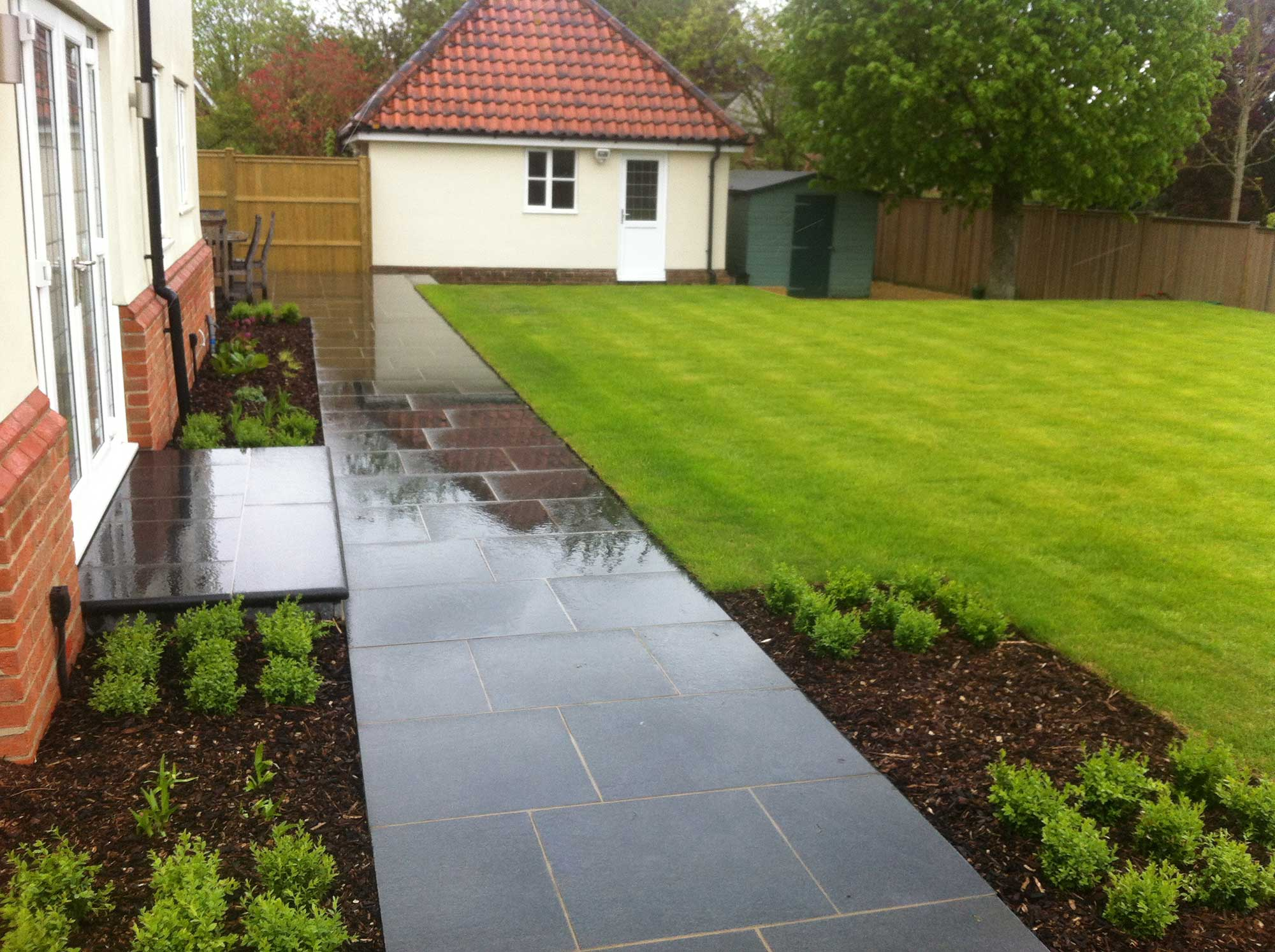 beautiful garden with black pavers and perfect lawn