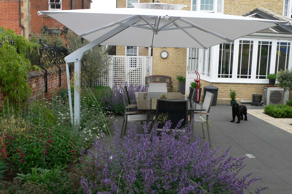 al fresco dining area in a garden in colchester with large patio umbrella and planting is shades of purple and green