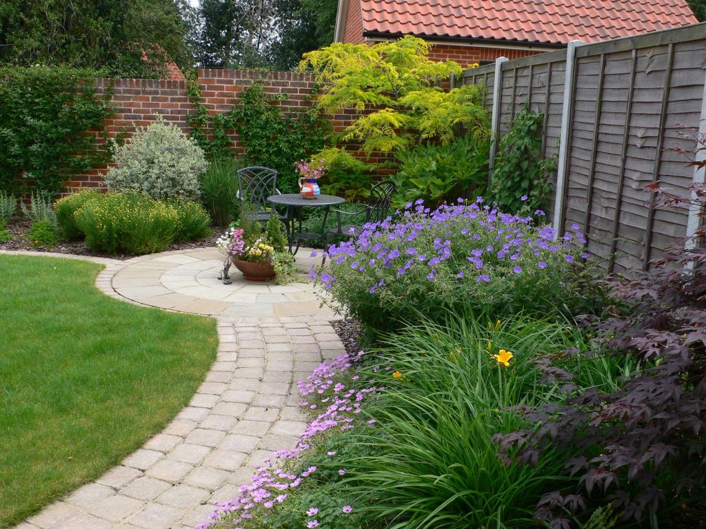 beautiful garden with curved path, circular seating area and lush planting