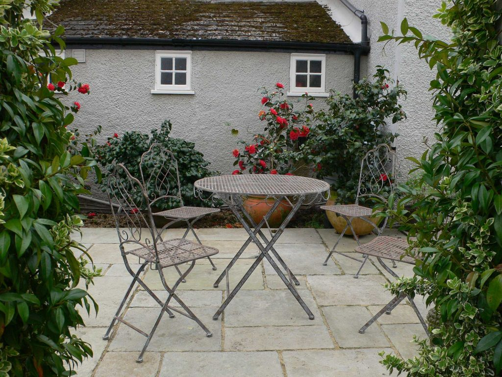 small courtyard garden with light grey paving, a small irong table and chairs