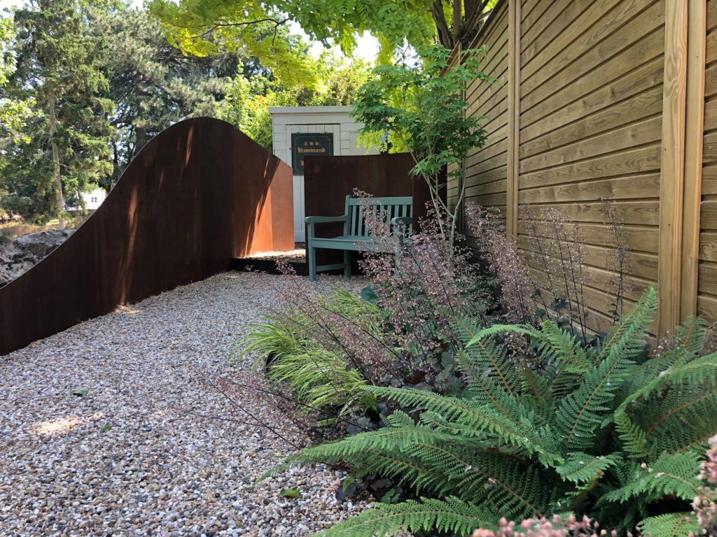 pathway to a shed with curved path and boundary walls