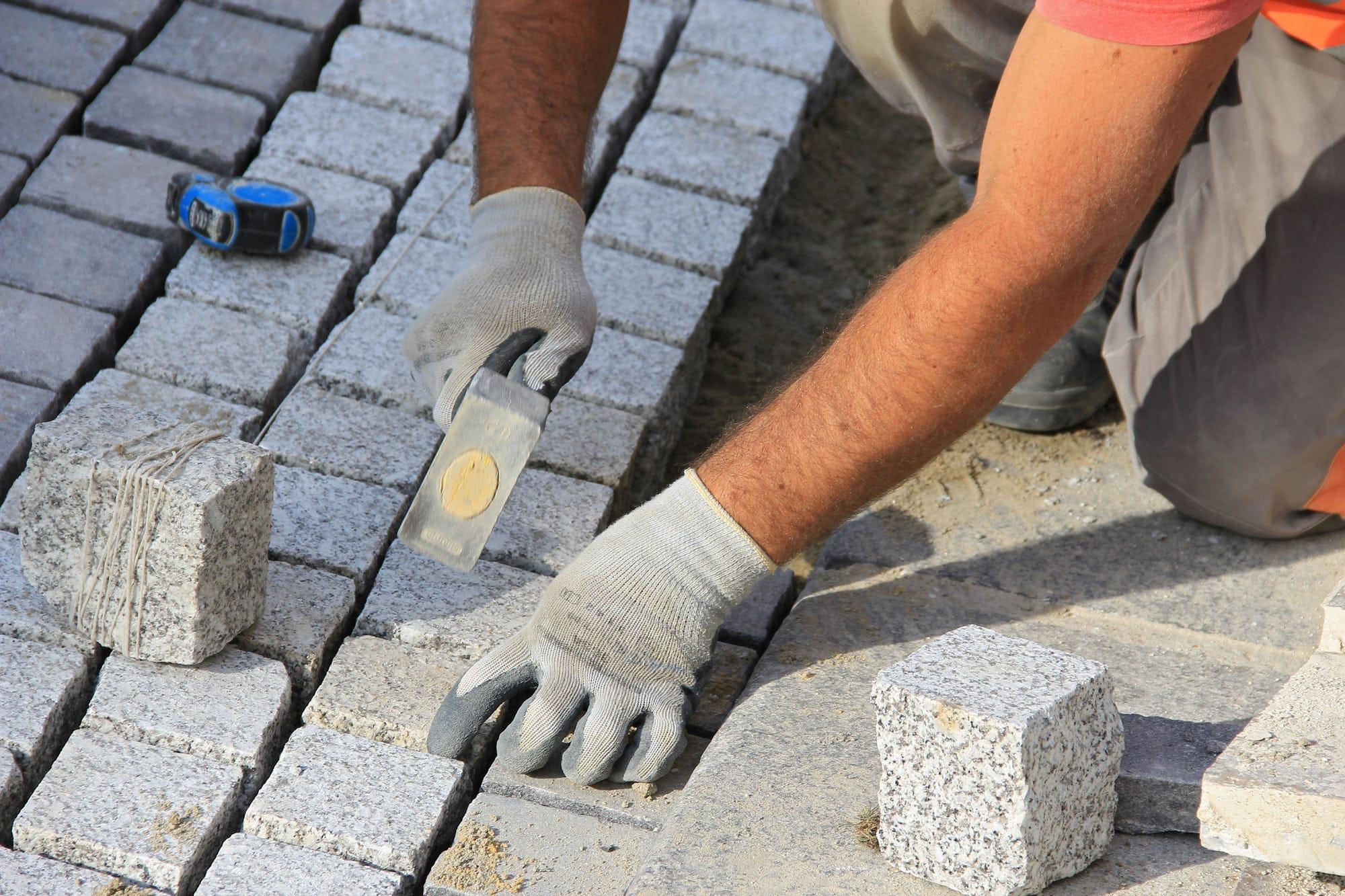 landscaper laying natural granite setts for a cobblestone driveway