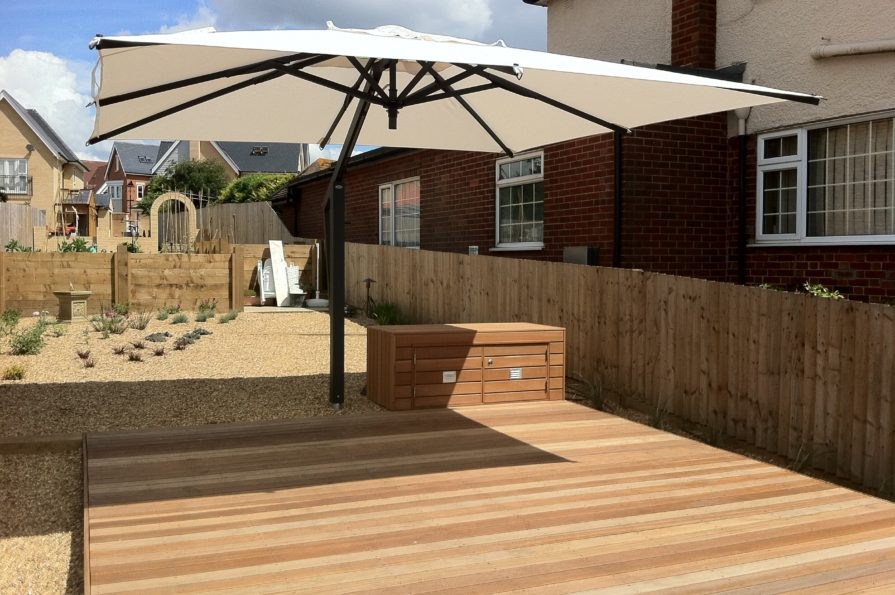 large decking project with sunshade and storage box in low maintenance garden