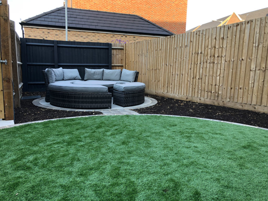 circular paved seating area in narrow garden with artificial grass in foreground