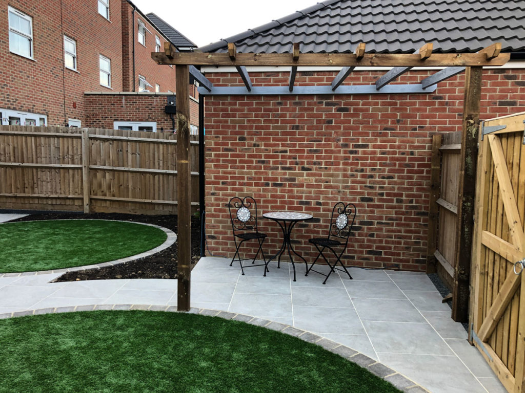 timber pergola beside a garage with porcelain patio and artificial grass