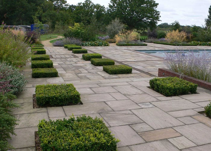 sandstone patio with clipped box hedges
