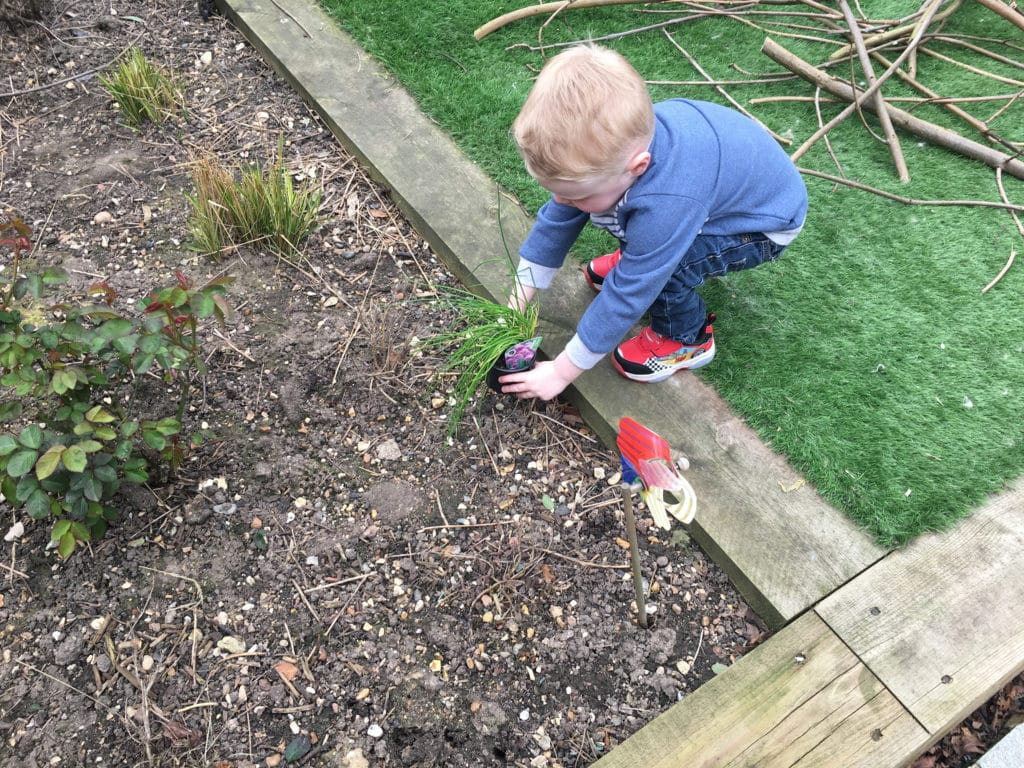 toddler planting herbs in the garden