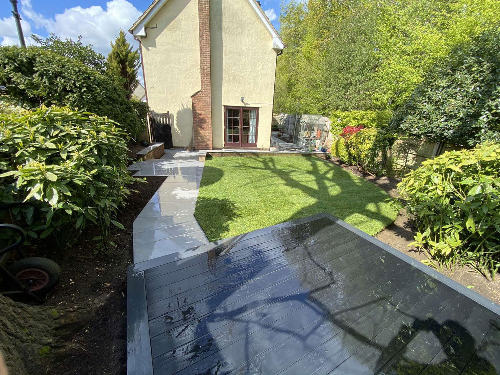 composite decking at the end of a mid sized garden looking onto lawns and planting