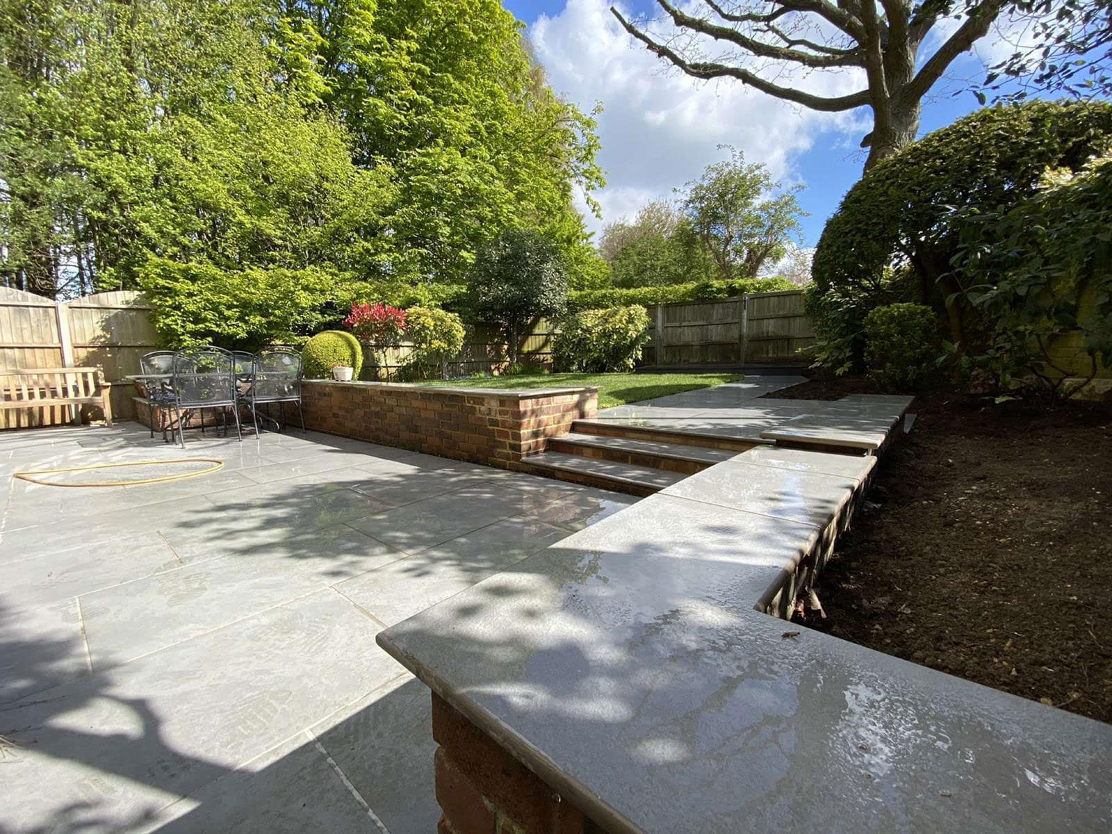 Attractive patio in mid sized garden with trees in the background
