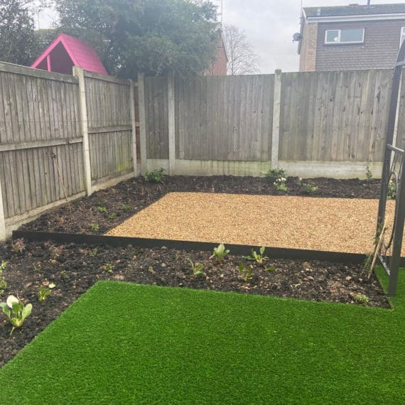 artificial lawn leading to planting beds and patio area