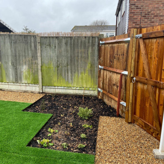 garden fence and gate with planting beds in front