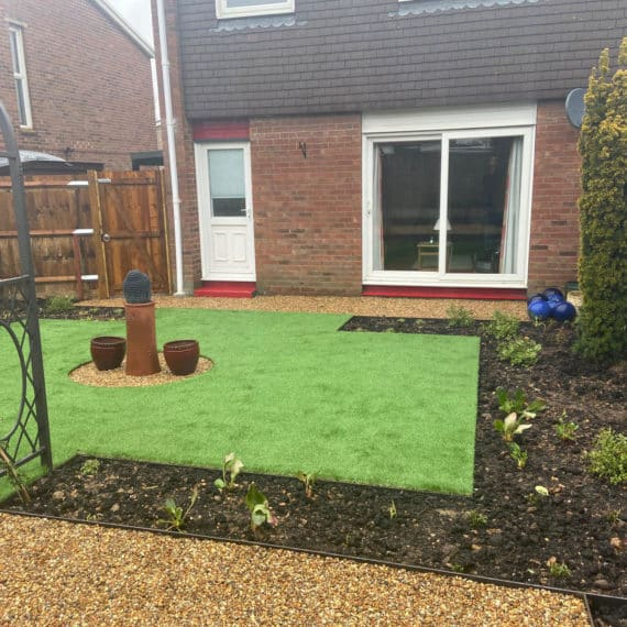 patio doors leading to artificial grass lawn with central ornament