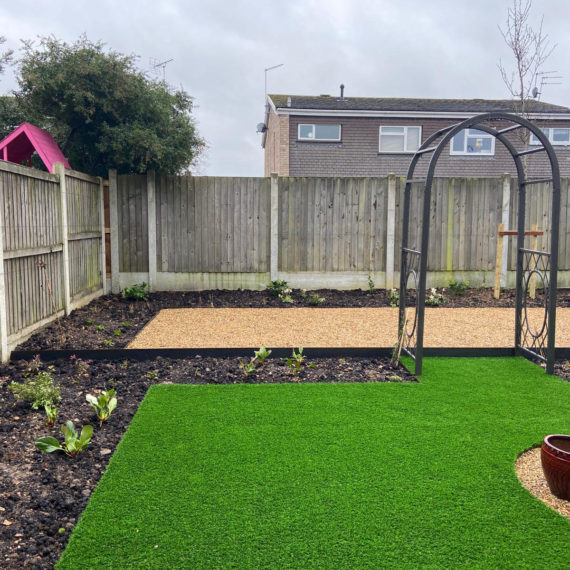 easy care garden with artificial lawn and decorative arch